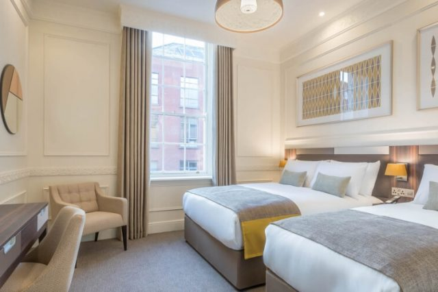 Hotel 7 Twin Room with a large double bed and a single bed